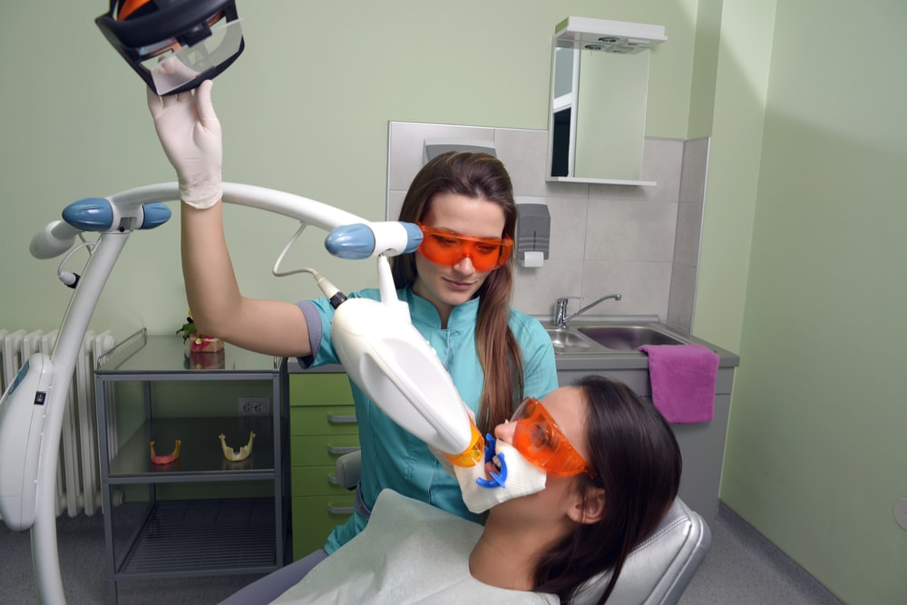 Patient with a light source device irradiating teeth whitening gel, during in-office procedure