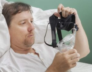 Image of a man holding and examining his CPAP mask